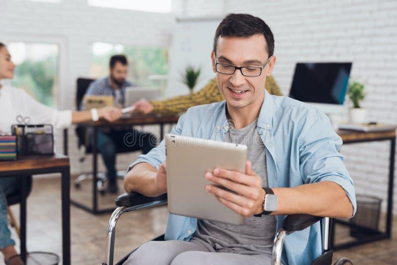 轮椅的残疾人在办公室工作 在他的手上是片剂 免版税库存图片