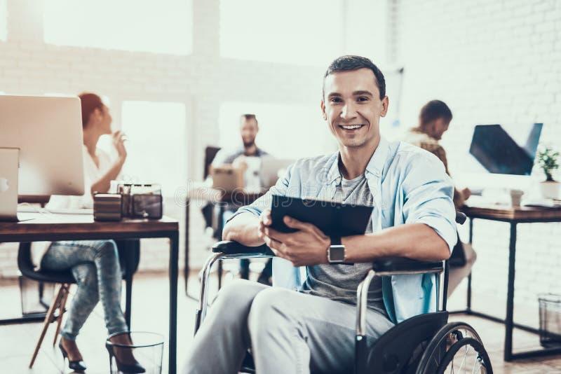 轮椅的残疾人有片剂的在办公室 库存图片