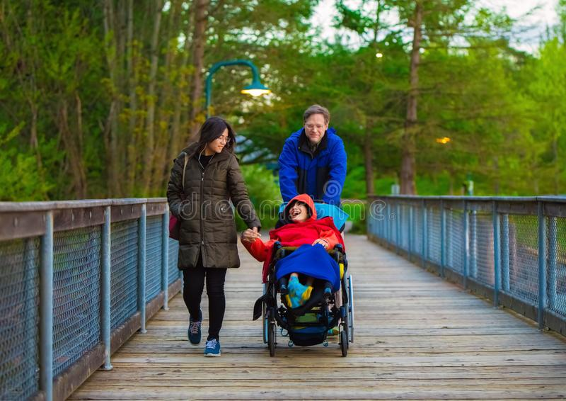 轮椅的残疾儿童在有父亲和姐妹的公园 图库摄影