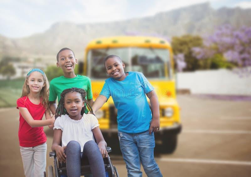 轮椅的残疾女孩有在校车前面的朋友的 库存图片