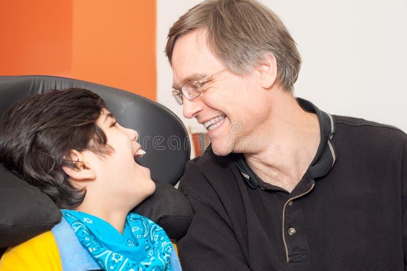 轮椅的残疾小男孩笑与hospit的父亲的 免版税库存照片