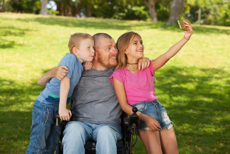 轮椅的残疾父亲 免版税图库摄影