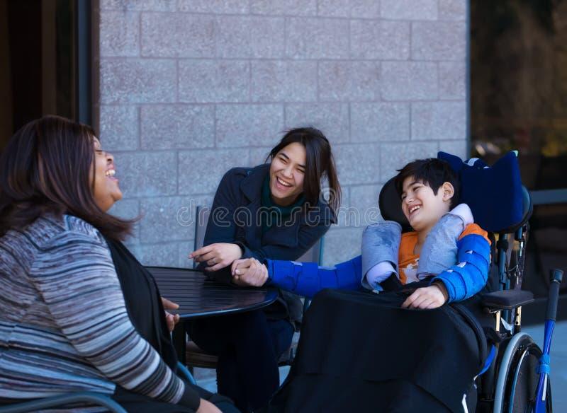 轮椅的残疾男孩在桌上户外谈话与caregi 图库摄影