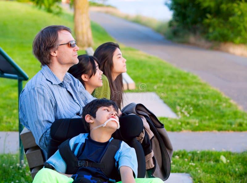 轮椅的残疾男孩有户外家庭的在晴天坐 库存图片