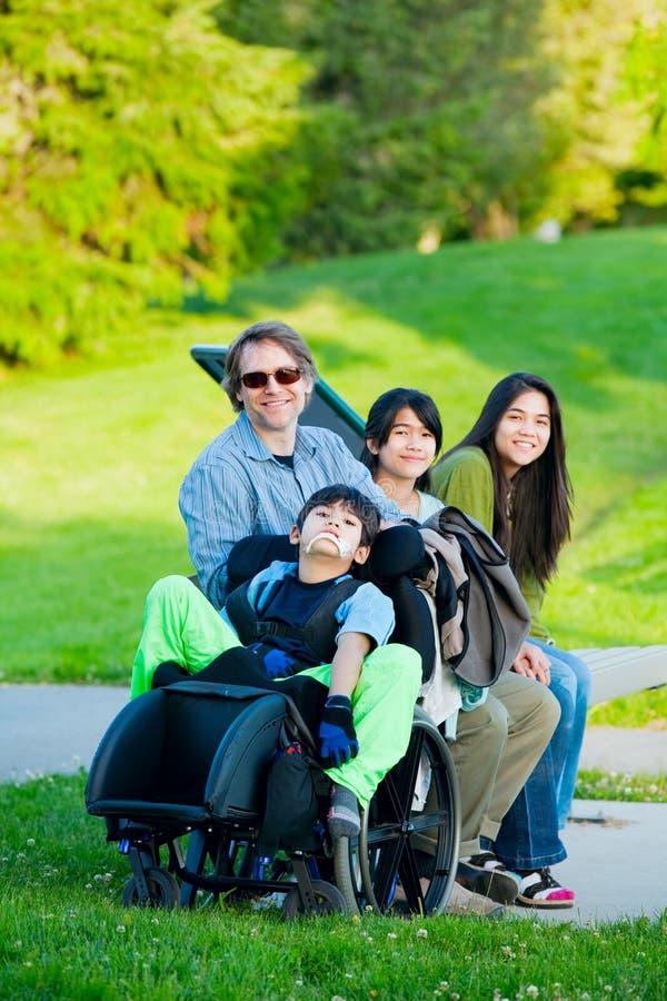 轮椅的残疾男孩有户外家庭的在晴天坐 免版税库存照片