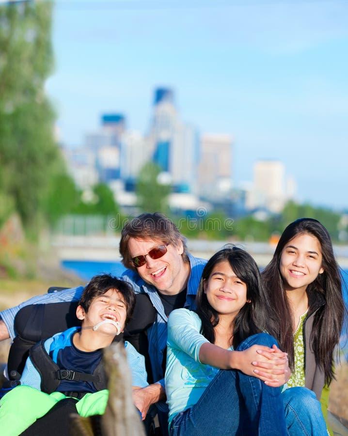 轮椅的残疾男孩有户外家庭的在晴天, wi 免版税图库摄影