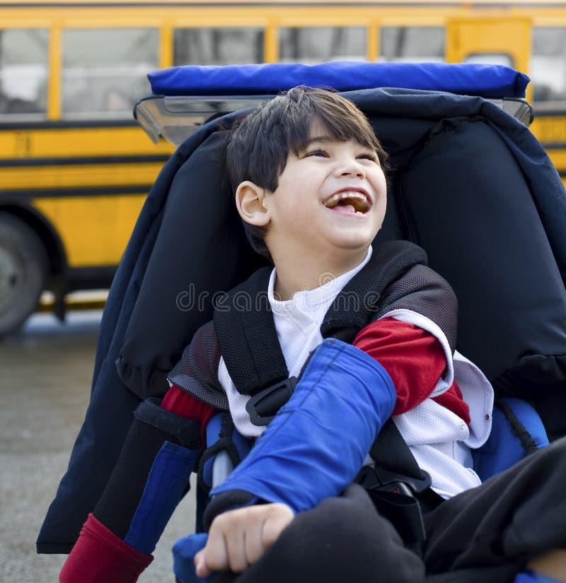 轮椅的残疾男孩,乘公共汽车 库存图片