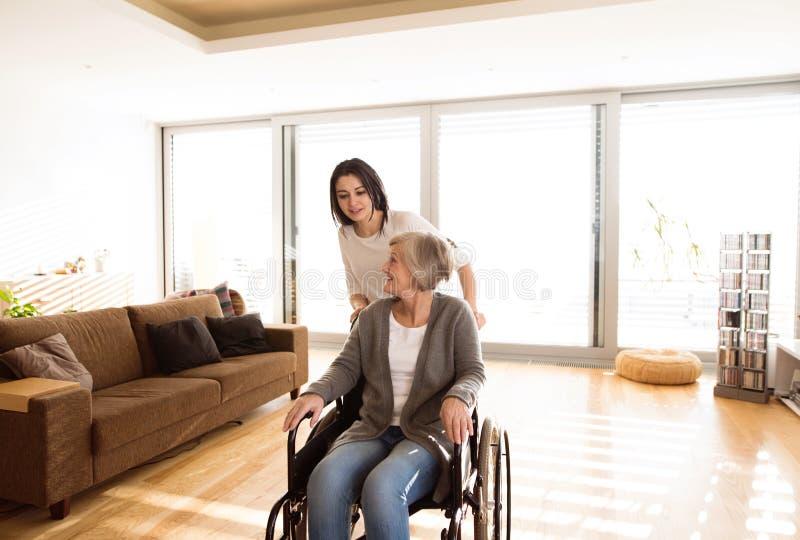 轮椅的残疾资深妇女有她的年轻daugher的 免版税库存照片