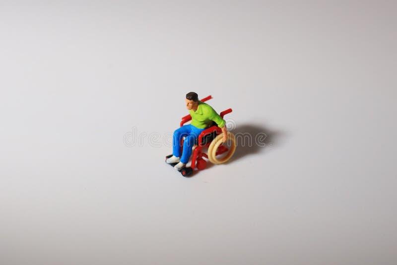轮椅的比例模型人在船上 库存图片