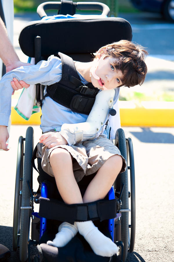 轮椅的父亲帮助的残疾儿童 库存图片