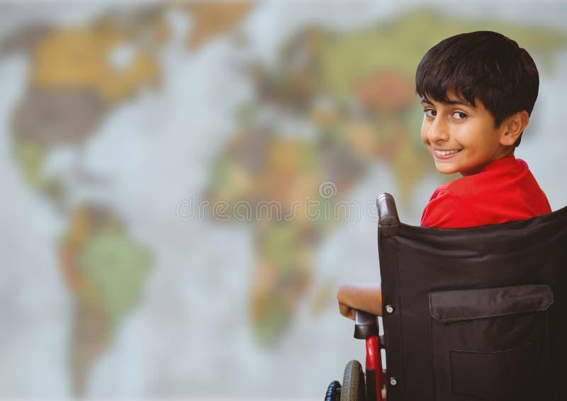 轮椅的男孩反对模糊的地图 库存图片