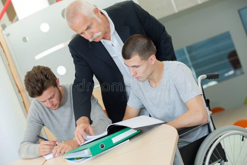 轮椅的男孩在类 免版税库存图片