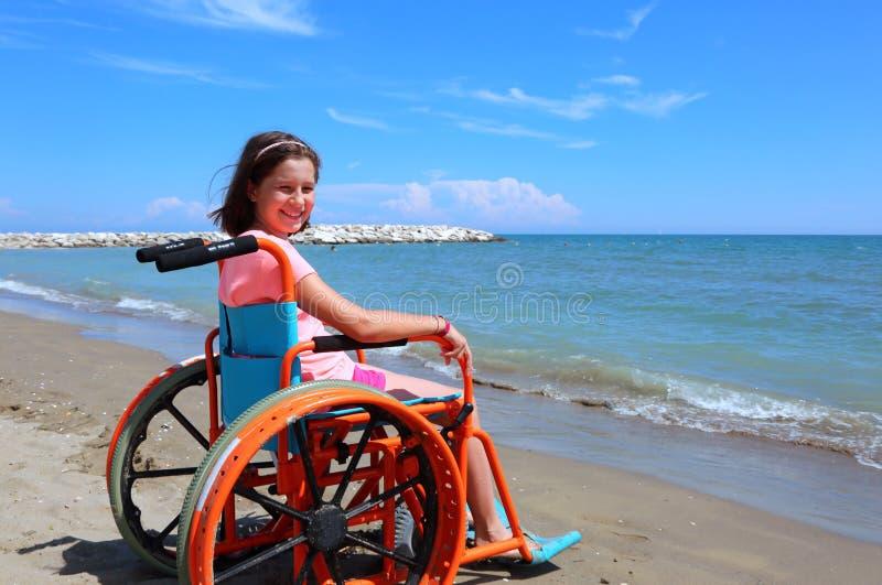 轮椅的白种人小女孩在海滩 库存图片