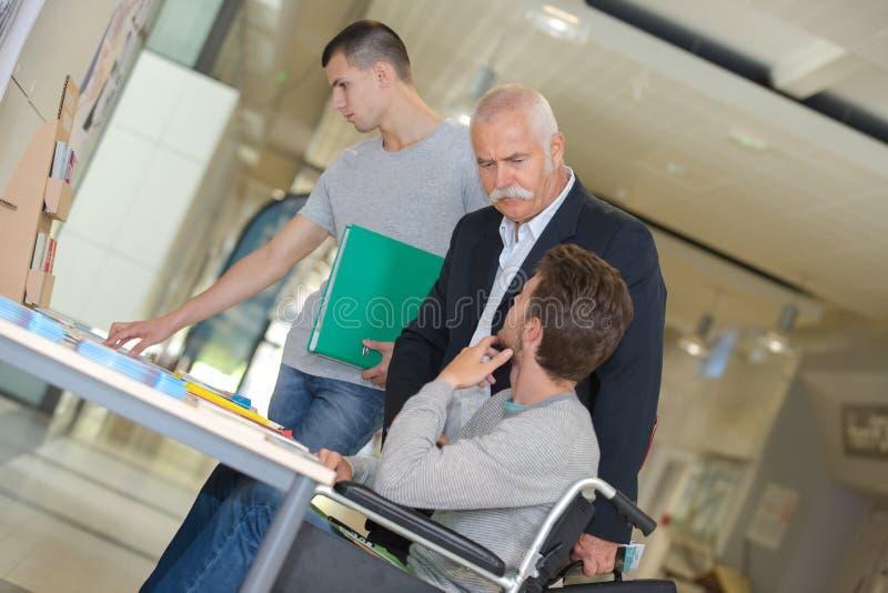轮椅的老师帮助的学生 免版税库存图片