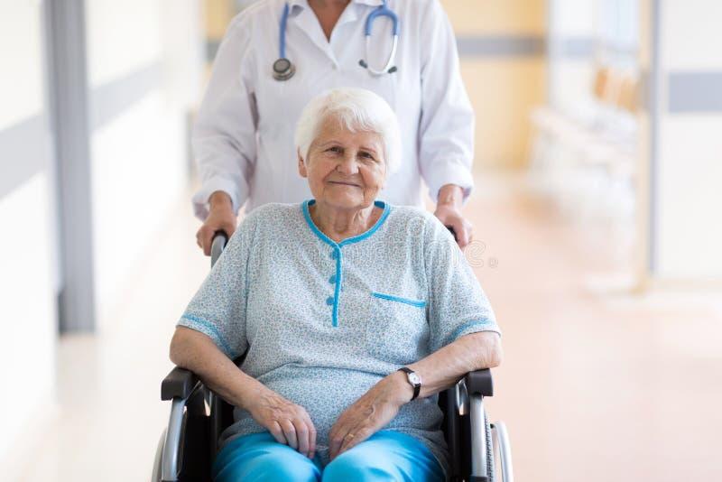 轮椅的资深妇女有医生的在医院 免版税库存照片