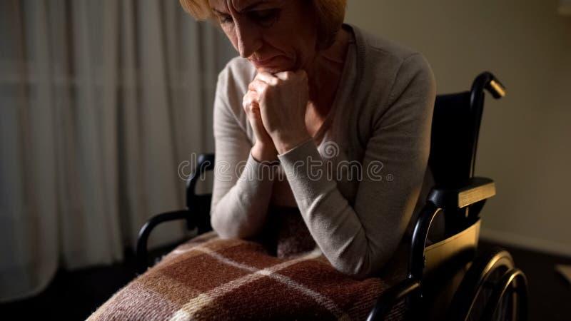 轮椅祈祷的上帝的成熟妇女,请求健康对所有她的亲戚 免版税库存图片