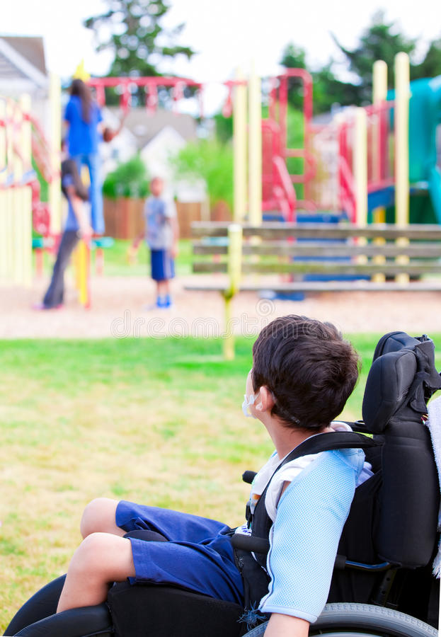 轮椅观看的儿童游戏的残疾小男孩在戏剧 库存照片