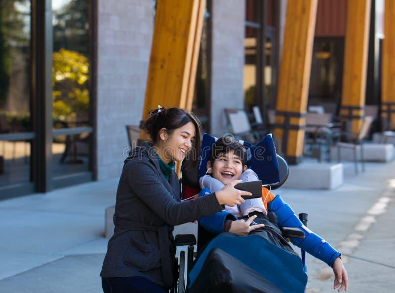 轮椅观看的录影的残疾男孩在有汽车的智能手机 库存图片