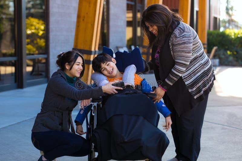 轮椅观看的录影的残疾男孩在有汽车的智能手机 免版税库存照片