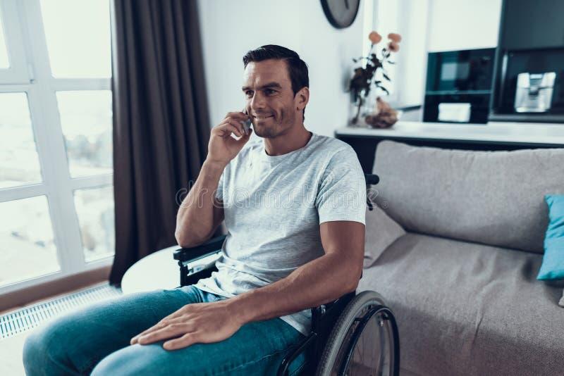 轮椅谈的电话的残疾人 免版税库存图片