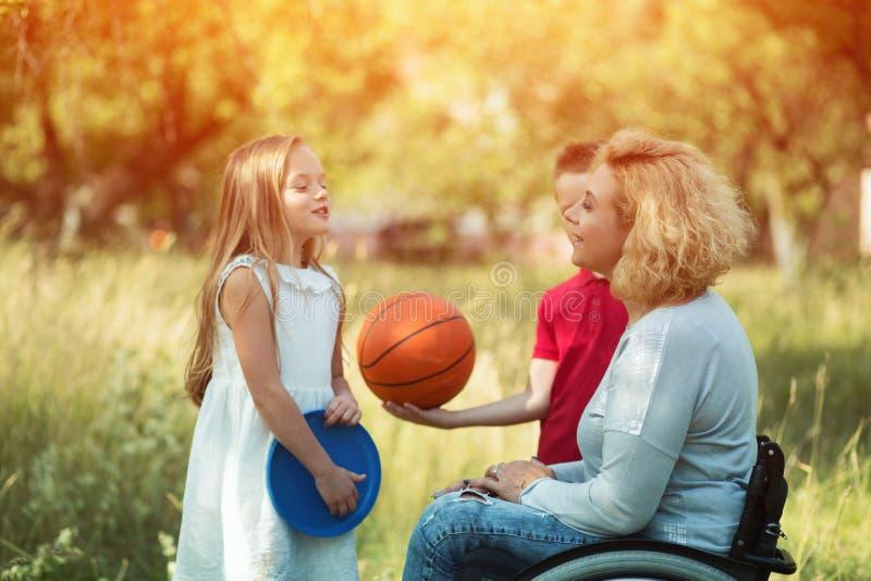 轮椅谈话的俏丽的妇女与孩子 免版税库存照片