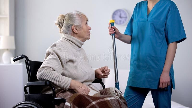 轮椅闲话的与医院管理员,寂寞健谈老妇人 免版税库存照片