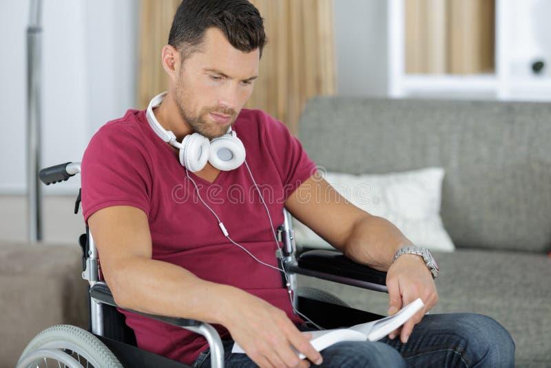 轮椅阅读书的年轻人在家 免版税图库摄影