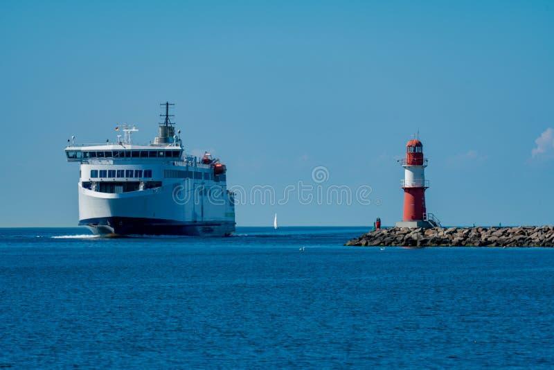 轮渡和烽火台在码头在Warnemuende 库存照片