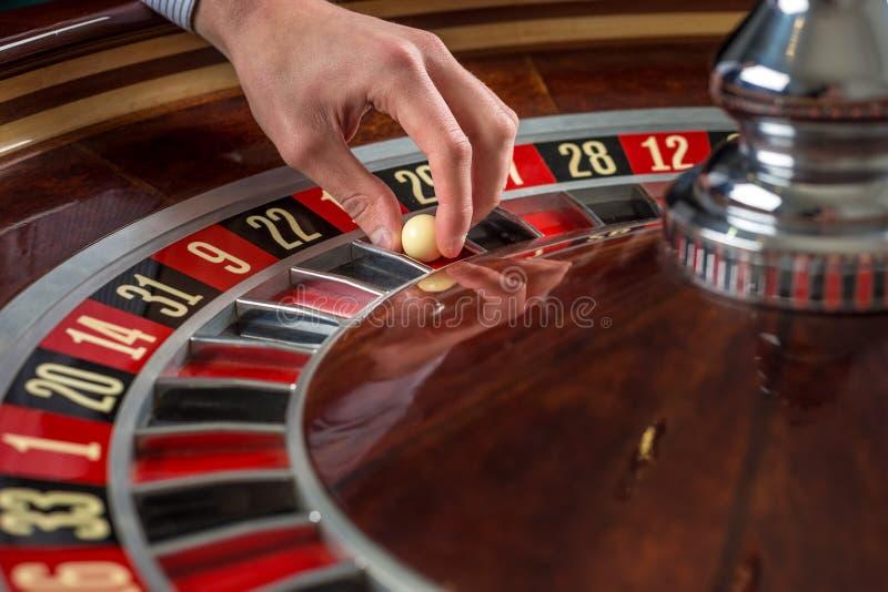 轮盘赌的赌轮和副主持人手有白色球的在赌博娱乐场 图库摄影