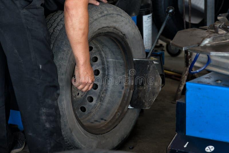 轮胎变动特写镜头,技工在车间更换在平衡器的车胎工程师平衡的车轮 免版税库存照片
