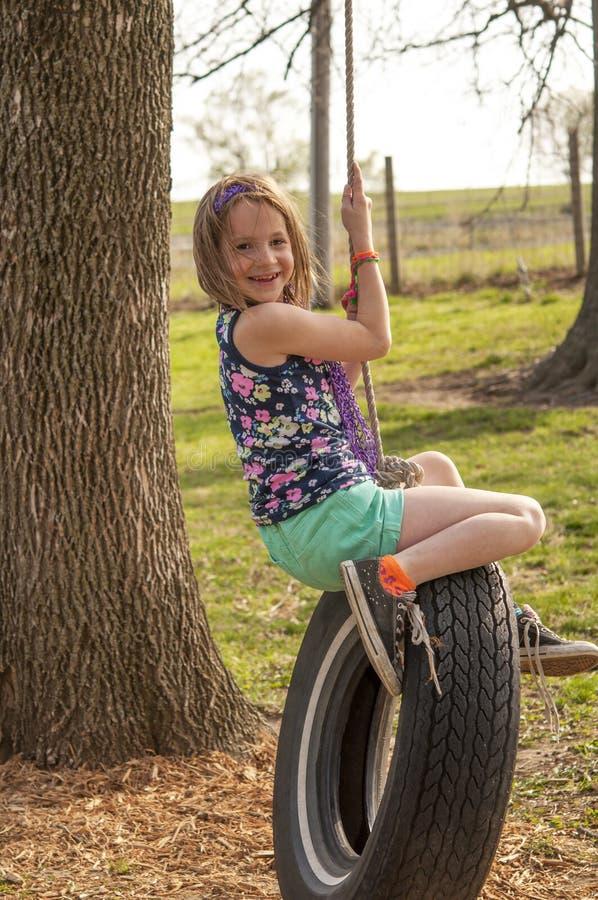 轮胎摇摆的女孩 免版税库存照片