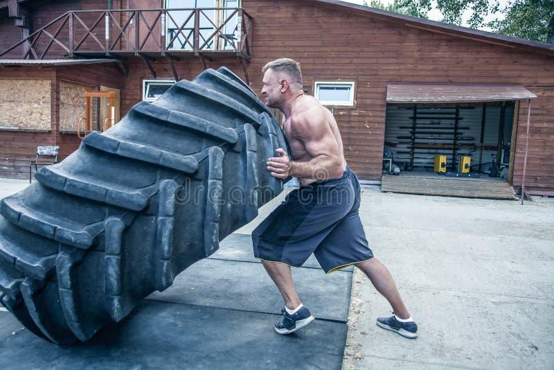 轮胎轻碰锻炼 运动员参与与重的轮胎的锻炼在街道健身房 举的概念,锻炼训练 库存照片