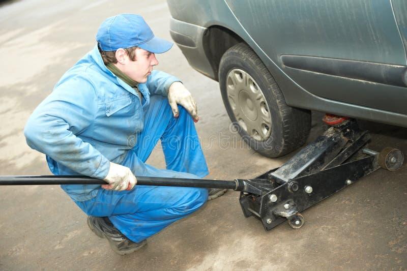 轮胎配件的Machanic安装工有汽车插孔的 免版税库存图片