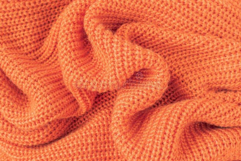 软性从橙色蓬松毛线的被编织的织品 免版税库存图片