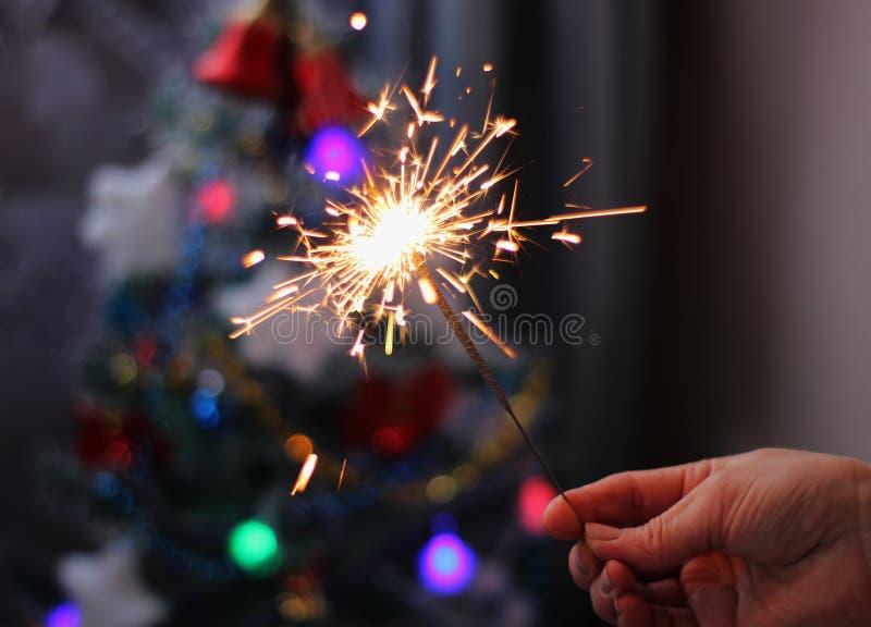 软性和迷离构想 拿着一个灼烧的闪烁发光物特写镜头的女性手 圣诞节新的s年 库存照片