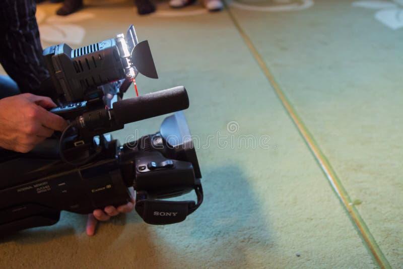 软焦点和模糊专业摄影师和摄象机操作员与他的专业设备一起使用 免版税库存图片