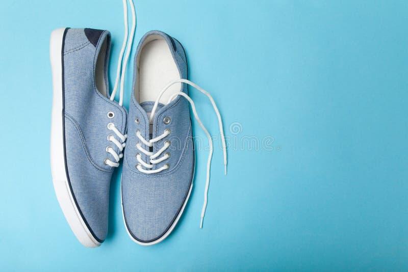 软的在蓝色背景的夏天舒适的蓝色运动鞋 r 免版税库存照片