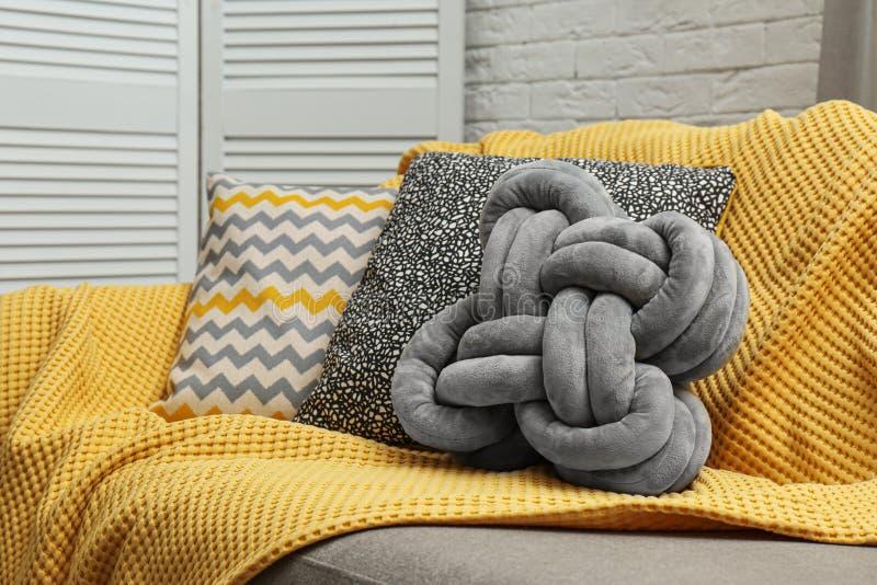 软的枕头和黄色格子花呢披肩在沙发在居住 免版税库存图片