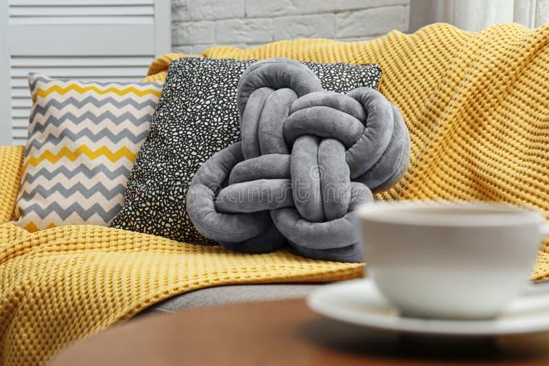 软的枕头和黄色格子花呢披肩在沙发 库存照片
