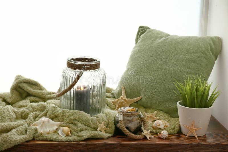 软的格子花呢披肩、枕头、燃烧的蜡烛和贝壳在窗台 库存图片