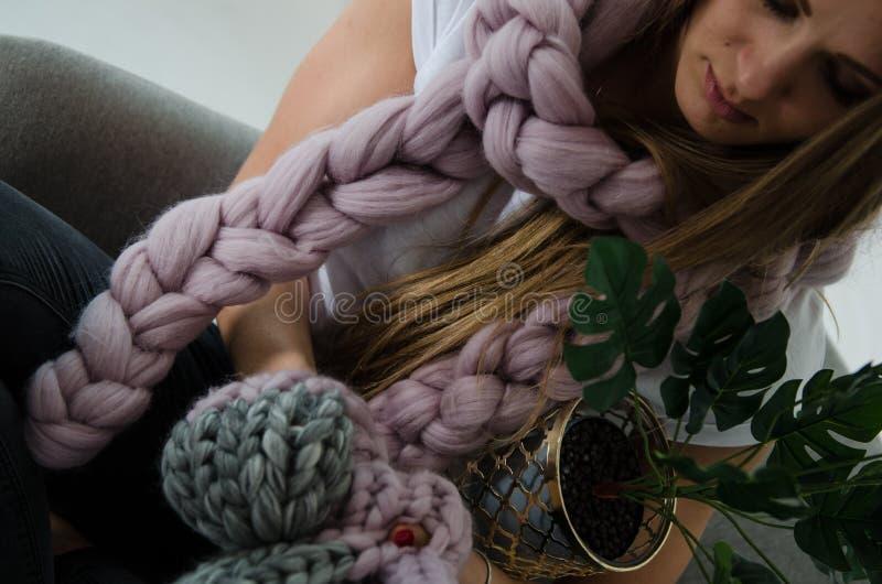 软的桃红色美利奴绵羊的羊毛围巾、帽子和手套的美丽的妇女坐胳膊椅子 免版税库存照片