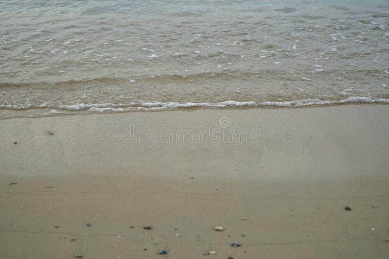 软的沙子和小岩石靠岸与海水和白色泡沫似的波浪背景和copyspace在Ornos岸 图库摄影