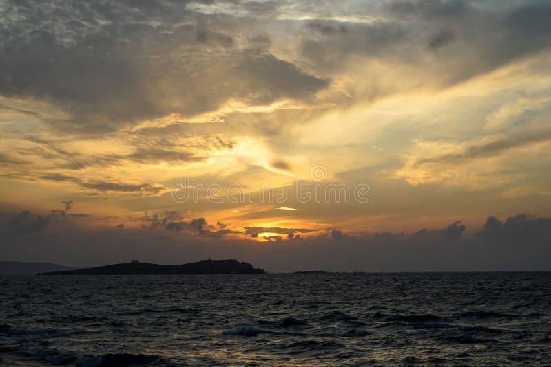 软的淡色橙色和蓝色日落颜色天空和抽象云彩背景美丽的树荫与有风波浪seaview 免版税库存照片