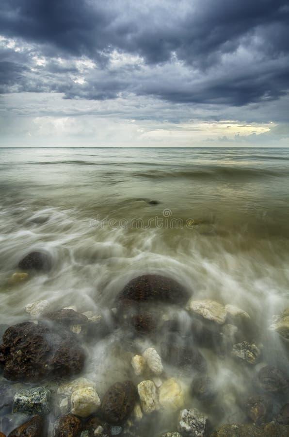 软的焦点和被弄脏的击中岩石的图象波浪在海滩 免版税库存照片