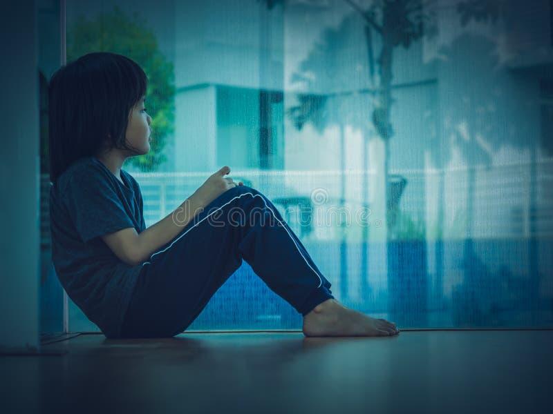 软的焦点小男孩不快乐的哀伤的开会在空的屋子里 库存图片