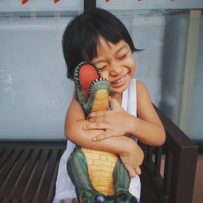 软的焦点照片葡萄酒样式儿童亚洲女孩愉快地拥抱恐龙玩偶 她是微笑的非常愉快,愉快的儿童女孩概念,是 免版税库存图片