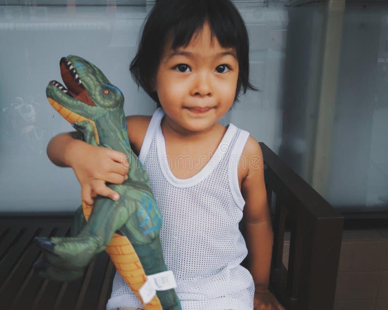 软的焦点照片葡萄酒样式儿童亚洲女孩愉快地拥抱恐龙玩偶 她是微笑的非常愉快,愉快的儿童女孩概念,是 免版税库存照片