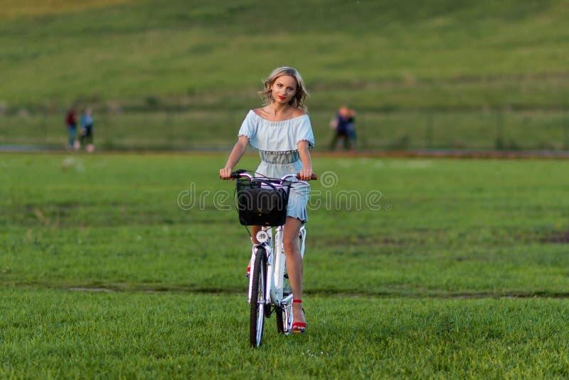 软的焦点照片 有一辆白色自行车的一名年轻,美丽的白肤金发的妇女在一个绿色草甸 免版税库存图片
