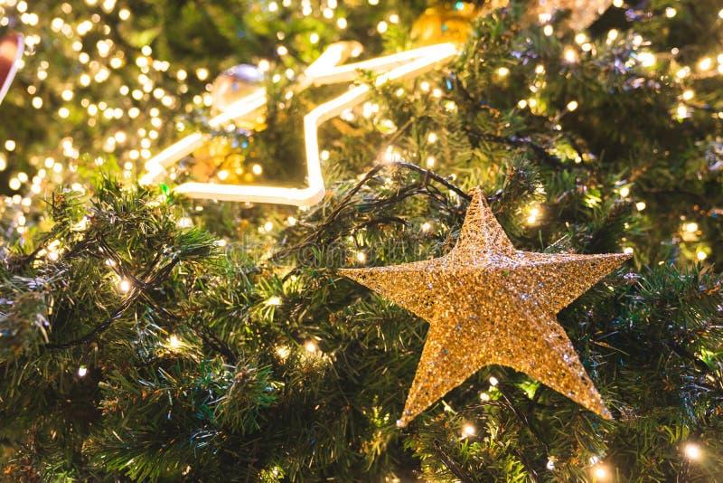 软的焦点闪闪发光在杉木圣诞树装饰的星装饰品和光的关闭 库存照片