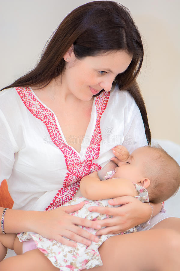 软的照片年轻母亲哺养的乳房她的婴孩 库存照片